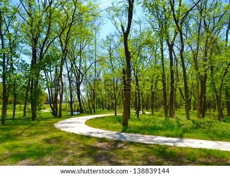 Paved Pedestrian Trail Follows Along a Winding Stream Through Woods in a Park  - Shutterstock ID 138839144
