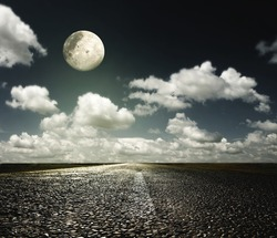 paved road in the night sky with the moon
