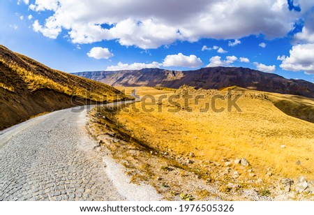 Paved road through a mountain valley under a cloudy sky. Mountain paved road. Road in mountain valley