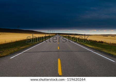 Paved road through Alberta Farmlands with windmills at dawn