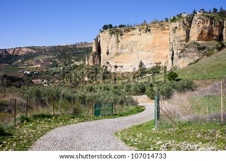 Paved road through the Andalusia countryside and rock of Ronda in Southern Spain, Malaga province.