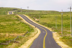 Paved two-lane road, Sir Francis Drake Boulevard, which leads to historic Point Reyes Lighthouse, across hilly grassland along Point Reyes National Seashore in northern California, USA, in spring