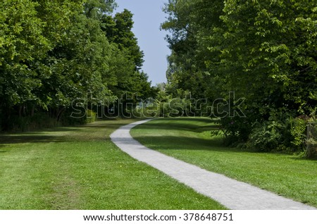 Paved walking path through a greenspace with deciduous trees and green grass. - Shutterstock ID 378648751