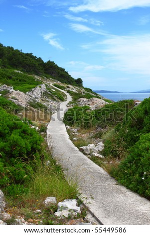 Paved walkway winding through rocky mediterranean landscape near the sea, island Losinj, Croatia - stock photo