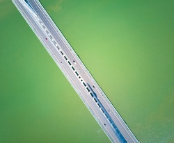 Pavement and vehicles of the bridge across the river, vertical aerial photography