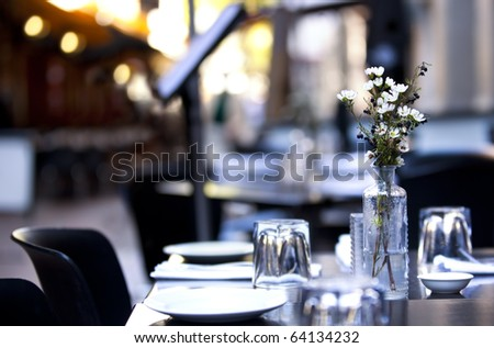 Pavement cafe table, with casual setting.  Focus on flowers, with blurred background.