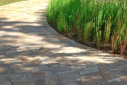 Pavement from Tiled Limestone In Garden landscaping. Backyard Garden Shaded Footpath from Tiled Stone Slabs. Flagstone Walkway in The Garden. Shady Pathway From Stone Tiles In The Park.