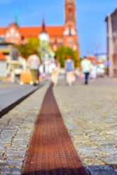 Pavers in central square of Kosciusko Market. On background Cathedral Basilica of Assumption of Blessed Virgin Mary in Bialystok, Poland. Selective focus on the pavement, blurred abstract background