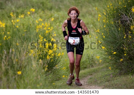 PAVIE, FRANCE - JUNE 23:Portrait of a female runner  at the Trail of Pavie, on June 23, 2013, in Pavie, France. All around her, gorse in full bloom.
