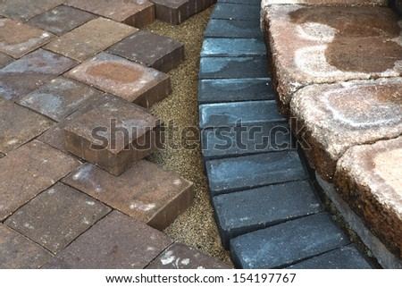 Paving around patio steps with different color tumbled pavers