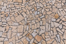 Paving blocks made of asymmetrical stone. The stone pavement as the background texture, Stone block road pavement