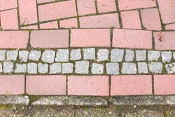 paving slabs, road markings, moss on the sidewalk, various stones near the road, as well as metal gratings and hatches