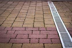 Paving stones in two colors with a hidden channel for rainwater runoff