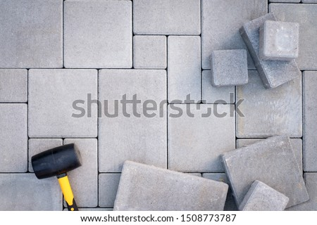 Paving stones paving background. Installing tools on foreground Stockfoto ©