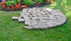 Paving stones removed from walk lying on grass being arranged in pattern. Home repair
