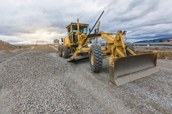 Paving the ground at road construction works with a bulldozer