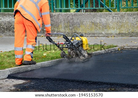 Paving worker uses vibratory plate compactor to compact new asphalt near curbstones  Foto stock ©