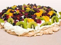 Pavlova dessert with kiwi, mango and berries
