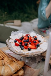 Pavlova dessert with whipped cream, strawberries and blueberries. dessert pavlova with berries on a plate top view. summer dessert for outdoor picnic parties close-up.