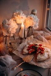 Pavlova's dessert with whipped cream and fresh strawberries, illuminated by the light of a burning candle. summer fresh dessert with strawberries and cream near a burning candle. vintage cake spoon