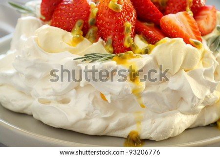 Pavlova with fresh strawberries and passionfruit ready to serve.