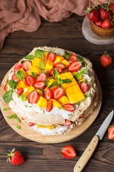 Pavlova with strawberries, mango and coconut cream. Cakes made of cane sugar. Tropical cake. Exotic dessert with mint. Strawberries on a wooden table. New Zealand food
