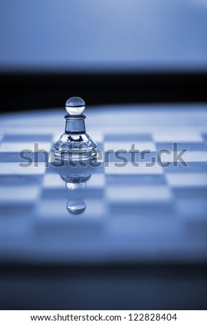 Pawn chess piece on chess board with reflection, in blue light - chess match or chess tournament. Copy / text space.