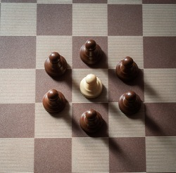 pawn on chess board surrounded by adversary concept of adversity ,discimination ,equality .