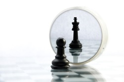 pawn pieces on the chessboard, the reflection in the mirror king, often in life things and people are not what they seem