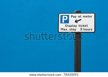 Pay at meter parking sign against a bright blue wall, UK