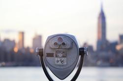 Pay binoculars in New York City with Manhattan skyline on background