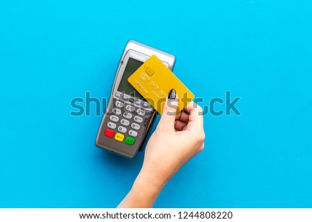 Pay by payment terminal. Paypass  technology. Woman's hand hold credit card, bring card to terminal  on blue background top view copy space
