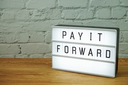 Pay It Forward word in light box with space copy on white brick wall and wooden background