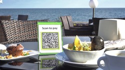 Pay touch-free with a QR code. QR code scanning app. Touchless digital payment option for businesses. A man sits in an open cafe on the beach