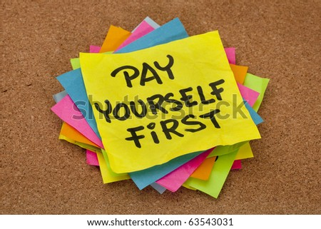 pay yourself first, a reminder of personal finance strategy - stack of colorful sticky notes on a cork bulletin board - stock photo