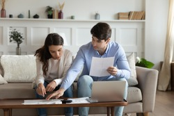 Payday. Concentrated attentive millennial spouses sitting on couch at home discussing possibility of taking out loan or credit, counting sum of taxes or bills to pay online using laptop and calculator