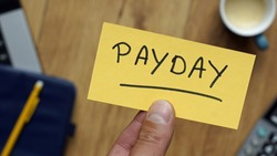 Payday written on a card at workingplace in business setting