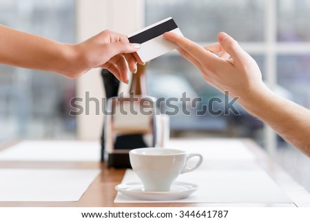 Paying arrangements. Waitress taking a credit card from customer who is offering it to her.