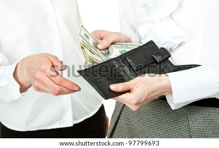 Paying money: closeup of woman's hands taking dollar banknotes out from wallet and giving them to other woman