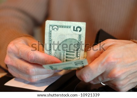 Paying The Bill With Twenty Five Dollars - Male hands holding a five and a twenty dollar bill and the check.  Shallow dof.