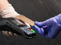 Paying with a gold credit card contactless Nfc at POS with medical gloves on black background. Nfc pay. Covid pay. Pos technology. Cashless payment during quarantine.