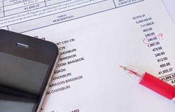 payment bill with red pen and phone.