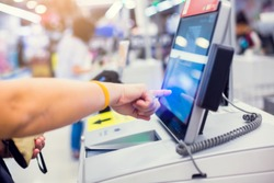 Payment blurry background image. Hand of woman customer is pressing the screen of the automatic payment machine. Self service machine in modern supermarket, self-service paypoint tills in hypermarket.