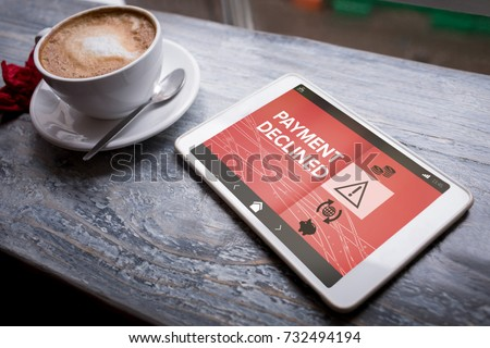 Payment declined text on phone screen against cappuccino and digital tablet on table