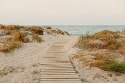 Payment Management Wooden path over the sand of the beach dunes