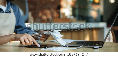 Payment of bills, bankruptcy and modern cafe during covid-19 quarantine. Millennial african american woman bartender in apron sits at table and works with laptop in interior of cafeteria, cropped