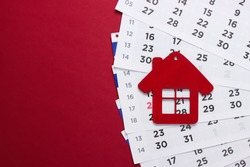Payment of rent for housing. Figurine of a house with a monthly calendar on a red background.