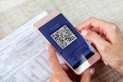 payment of utility bills by QR code without leaving the house, using a smartphone, the girl makes an on-line payment. Scanning Two-Dimensional Code with Mobile Phone