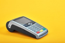 Payment terminal, compact POS terminal on yellow background top view copy space.