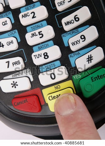 Payment terminal with a finger pushing a button. Close up